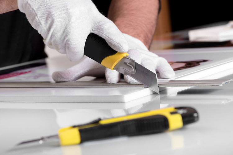 Cropped image of man using utility knife on table