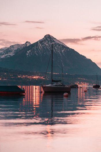 Sailboats on lake during sunset