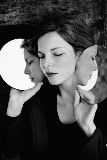 Close-Up Of Woman With Eyes Closed Holding Mirrors With Reflection