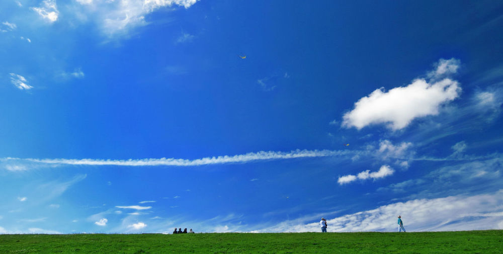 Scenic view of golf course against blue sky