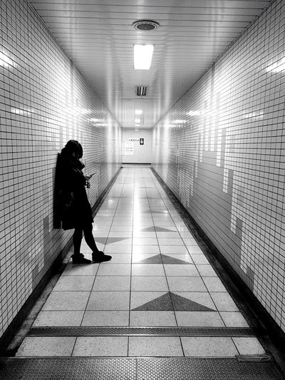 Full length of woman standing in building passage