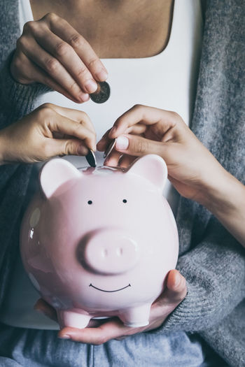 Hands putting coin in happy smiling piggy bank. saving money for household payments, bank bills.