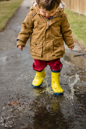 Toddler Playing In Puddle On Sidewalk In City