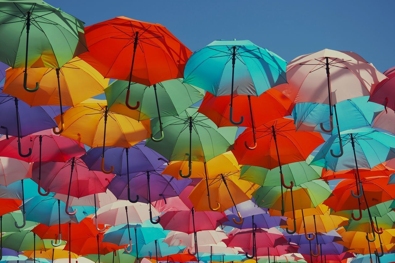 LOW ANGLE VIEW OF MULTI COLORED UMBRELLAS HANGING AGAINST SKY