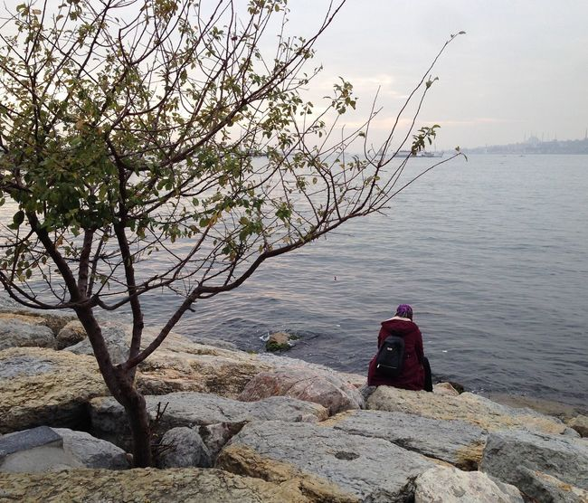 Sea Nature Real People Water One Person Rear View Rock - Object Beauty In Nature Tranquil Scene Tranquility Sitting Fishing Tree Lifestyles Women Leisure Activity Outdoors Scenics Men Day Colour Your Horizn