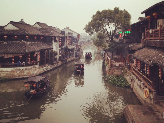 High angle view of people on boat in canal amidst traditional building