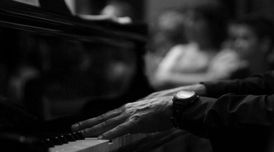 Side view of hands playing the piano