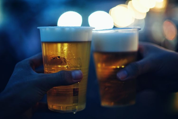 Cropped hands toasting beer glasses at night