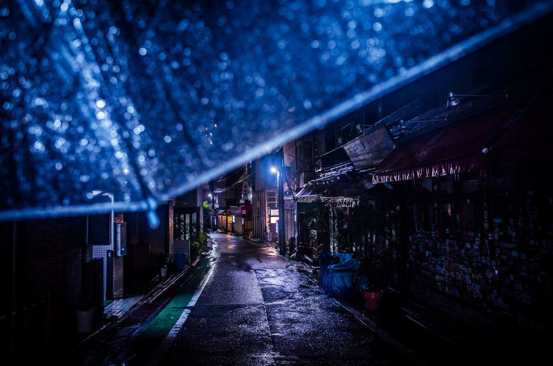 Cropped image of wet umbrella in alley at night