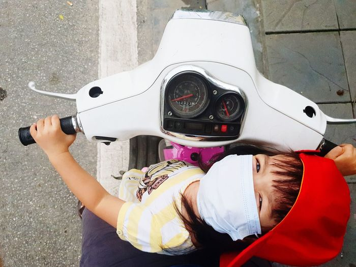 Portrait of girl wearing surgical mask while sitting on motor scooter at road