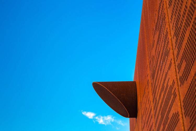 Low angle view of air duct on building against clear blue sky
