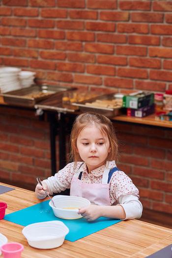 Girl looking away while making cake