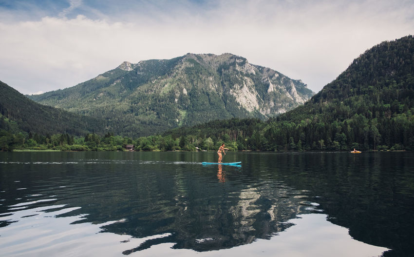 Woman paddleboarding in lake by mountains against sky