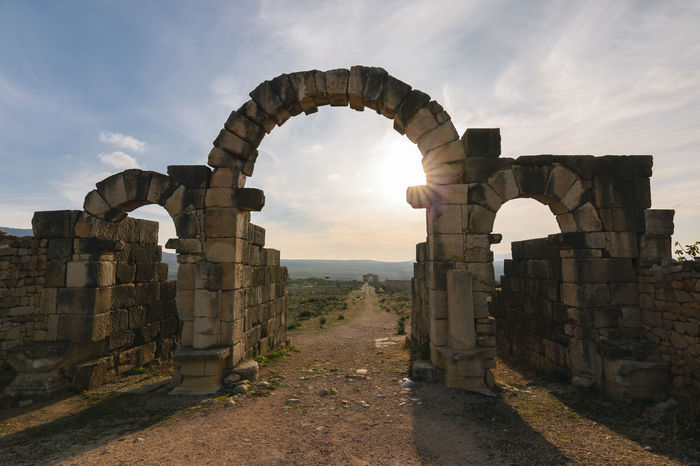 The Tingis Gate, looking back down the Decumanus Maximus in Volubilis on sunny day with few clouds, Morocco. Africa Ancient Arch Archaeological Archictecture Basilica Capitoline Column Culture Empire Gate Heritage Heritage Building Historical Landmark Meknès Morocco Old Oriental Roman Stone Temple Tingis UNESCO World Heritage Site Volubilis