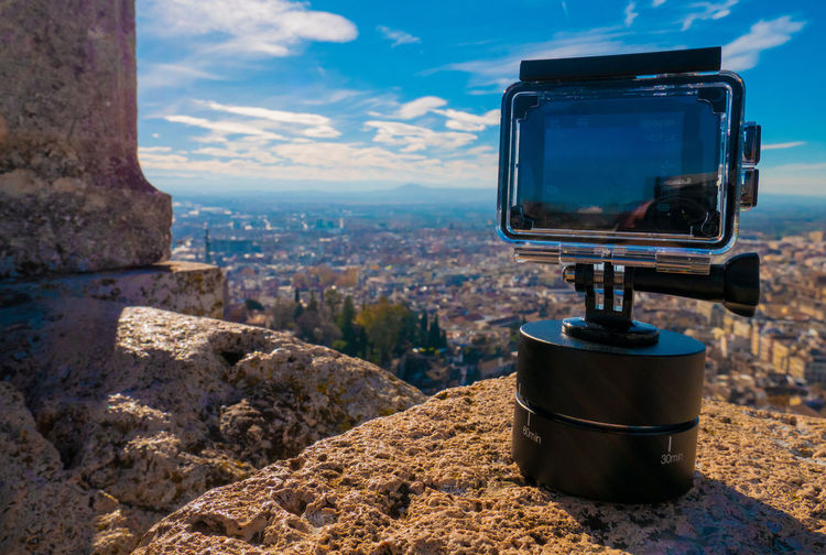Close-up of camera on rock against sky