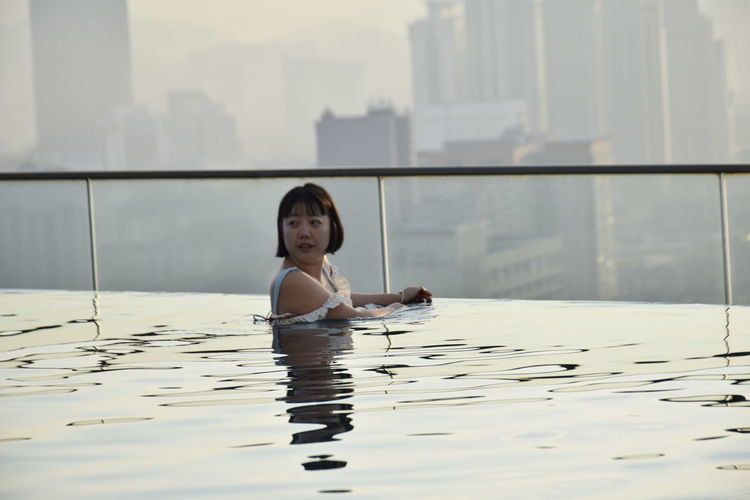 Side view of woman in infinity pool against buildings during sunset