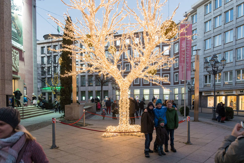 ESSEN, GERMANY - DECEMBER 04, 2016: Unidentified kids pose for a photo in front of an illuminated tree. Adult Adults Only Celebration Christmas Christmas Decoration Christmas Lights Christmas-market Xmas Christmss City City Gate Essen Getting Inspired Illuminated Large Group Of People Outdoors People Place To Visit Scenics Tree Urban Winter