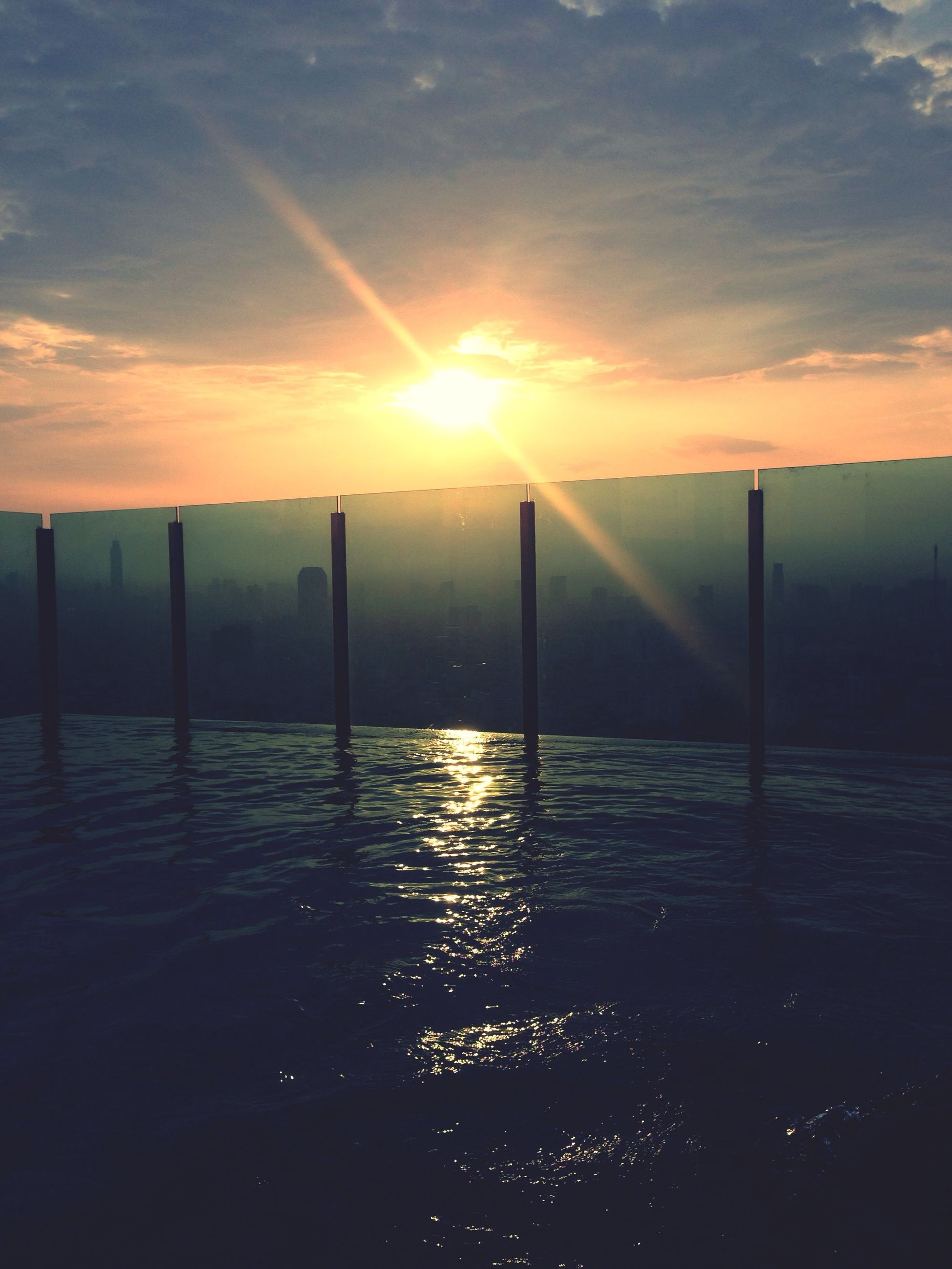 sunset, sun, water, sky, orange color, scenics, tranquil scene, tranquility, sea, beauty in nature, idyllic, sunlight, nature, reflection, silhouette, cloud - sky, horizon over water, cloud, pier, sunbeam