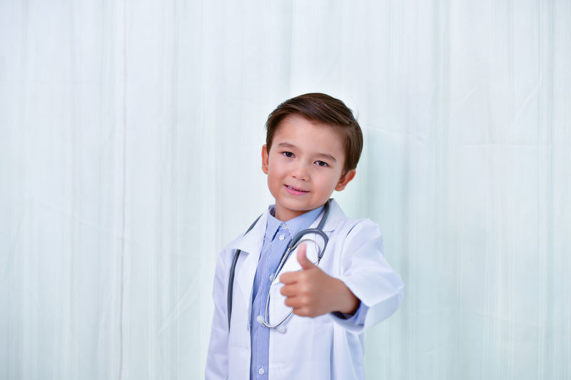 Young doctor Concept, The Young doctor is smiling on a white background. Check American Background Being Boy Caucasian Cure Diagnostic Doctor  Drug Equipment European  General Handsome HEAL Health Health Care Healthful Healthy Hospital Hypodermic Hypodermic Syringe Illness Inject Inspect Insurance Japanese  Kid Learning Life Lifestyle Listening Male Man Measurement Medical Medicate Medicine Patient Practitioner Preventative Secure Smiling Stethoscope  Student Study Syringe White Work Young