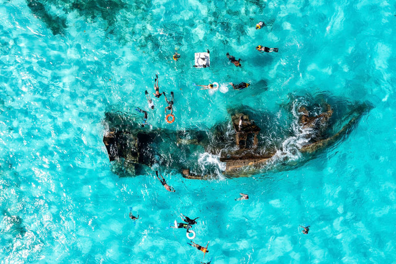 People snorkelling around the ship wreck near cancun in the caribbean sea.