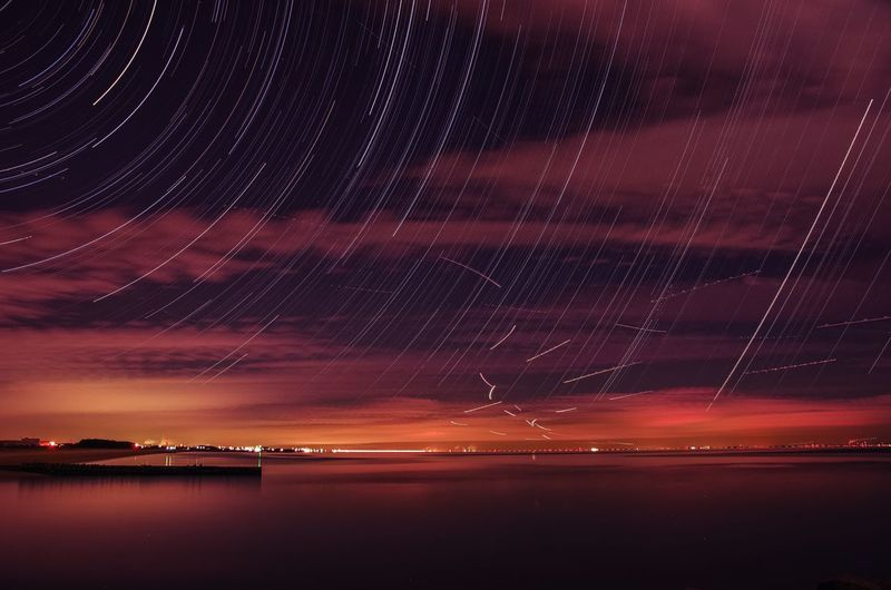 Scenic View Of Sea Against Star Trails In Dramatic Sky At Sunset