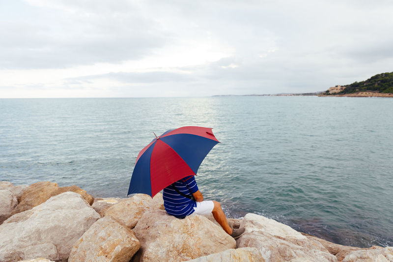 Person on rock by sea against sky