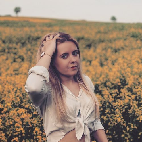 Portrait Of Beautiful Woman With Hand In Hair Standing Amidst Plants On Field