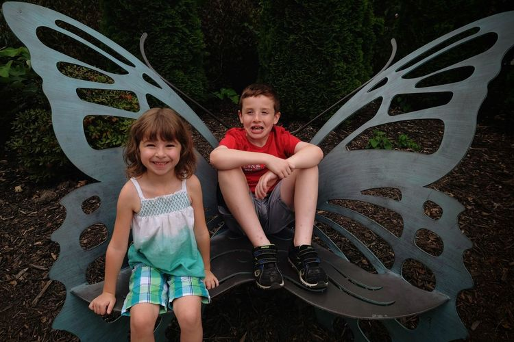 Portrait of siblings sitting on wing shaped chair