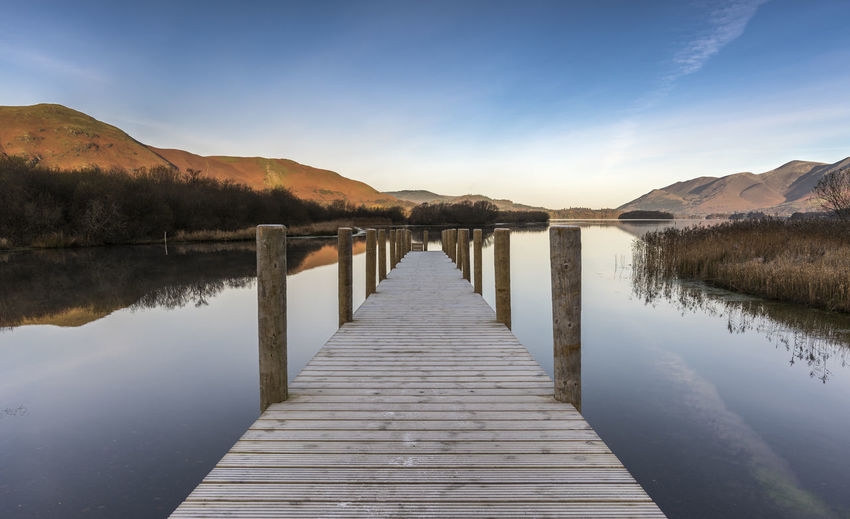 Reflections on a still frosty morning at Derwent Water - Cumbria Callander Colors Frost Beauty In Nature Cold Day Jetty Jetty View Lake Mountain Mountain Range Nature No People Outdoors Pier Reflection Room For Text Scenics Seasons Sky Still Life Tranquil Scene Tranquility Water Wood Paneling