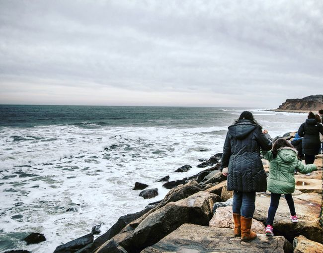Mother with daughter walking on rocky sea shore against sky
