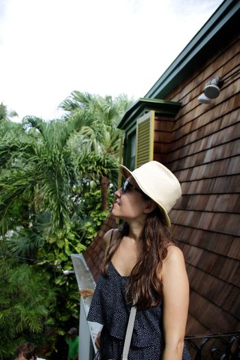 Woman in sunglasses and hat standing by house against sky