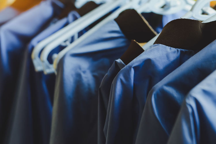 Stylish blue clothes hangers and beautiful blue shirts hang together.