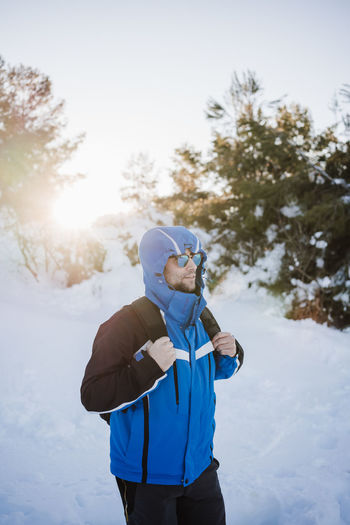Man wearing warm clothing standing on snow covered land during winter