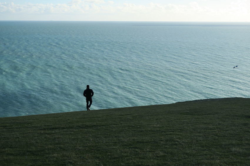 walking on the end of land Alone End Of Land English Channel Seven Sisters Hike Man And Bird Ocean One Man Only Sea Silhouette Solitude Tranquility