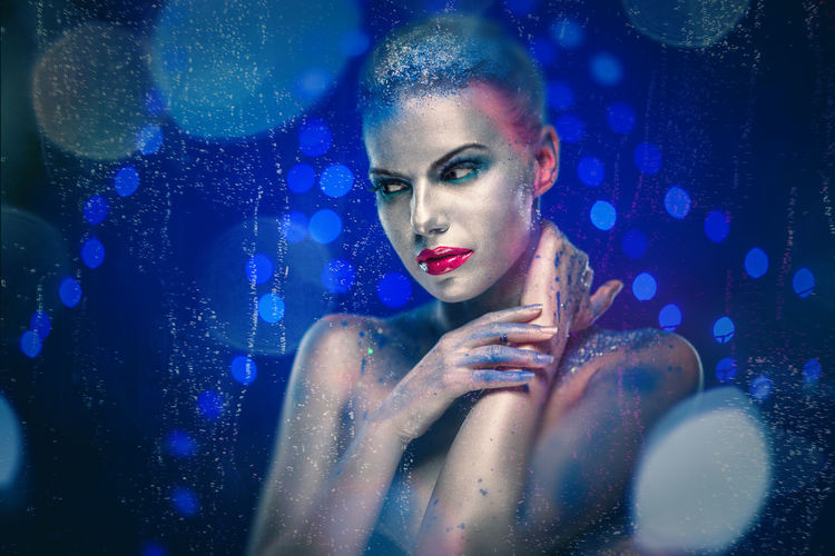 Young Woman With Glitter Against Blue Background