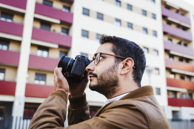 Close-up of man photographing with camera against building