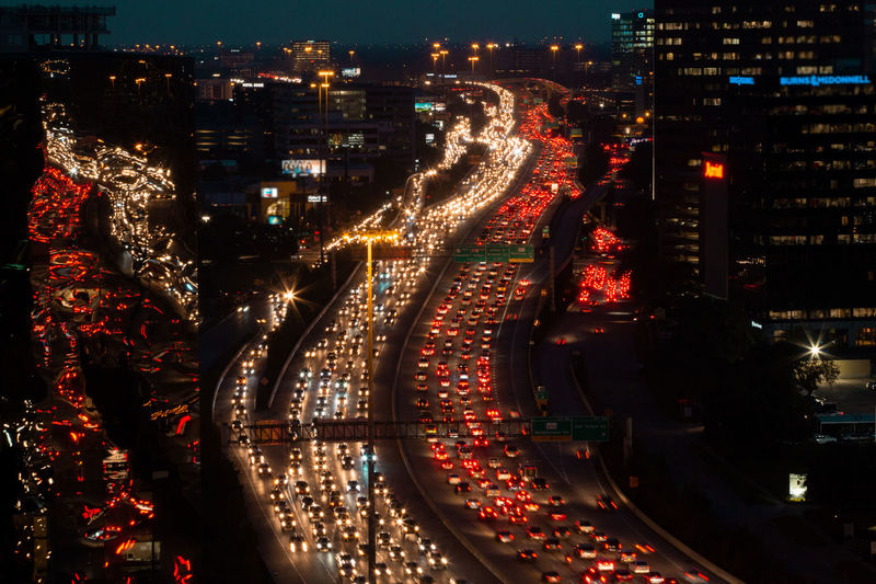Freeway jammed with vehicles at night. Traffic is reflected in building windows. Abstract Reflections City Life Commuting Transportation Urban Geometry Architecture City Life Cityscape Glowing Headlights High Angle View Illuminated Long Exposure Mode Of Transportation Motion Night Outdoors River Of Light Tail Traffic Traffic Jam City Urban Skyline