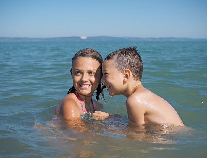 Siblings swimming in sea against clear sky