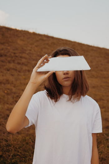 One Person Real People Leisure Activity Front View Standing Lifestyles Waist Up Casual Clothing Land Women Focus On Foreground Holding White Color Nature Day Brown Hair Adult Hairstyle Sky Teenager Minimalism Modern Reflection