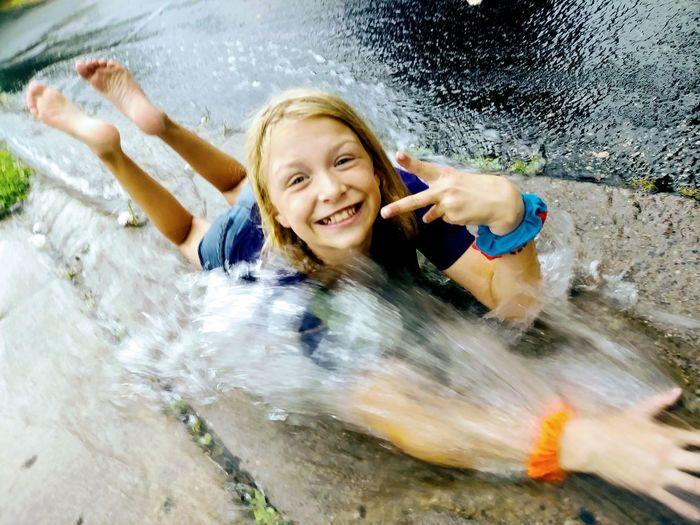 High angle view of water splashing on cheerful girl lying on road