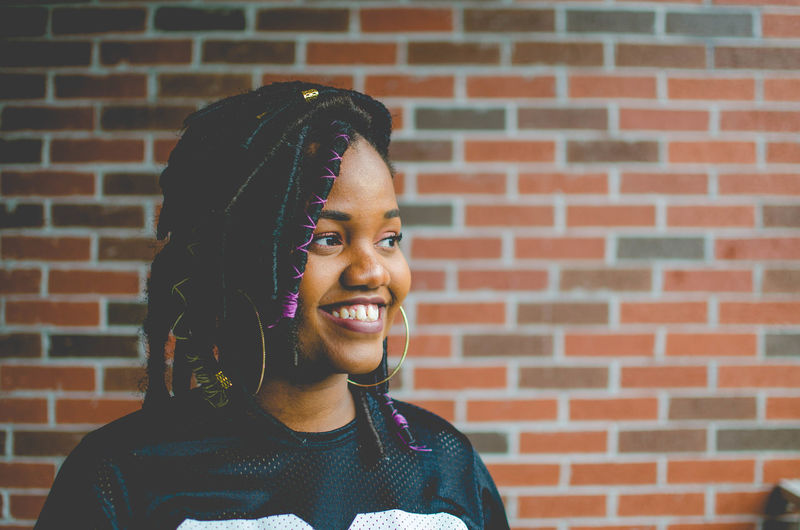 Close-up of smiling young woman standing against brick wall