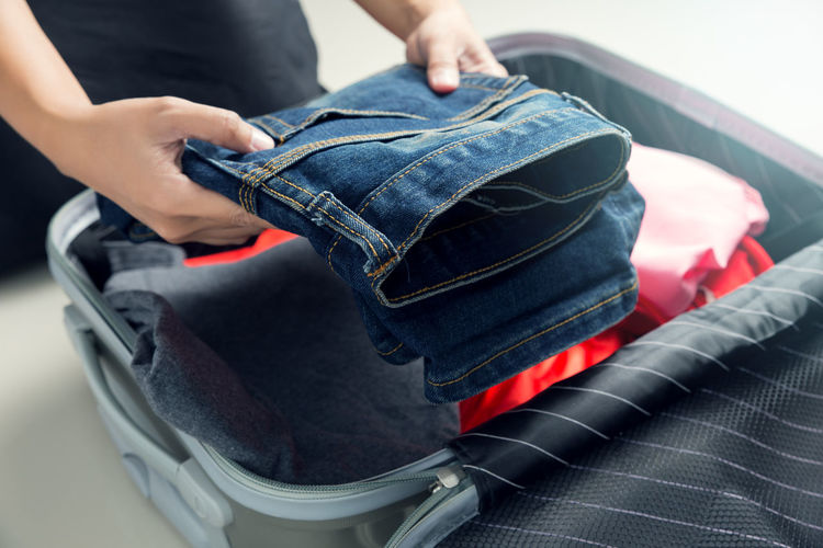 Woman packing clothes into travel bag Adding Bag Baggage Belongings Carryon Casual Clothing Close-up Day Human Body Part Human Hand Indoors  Jeans Leisure Activity Lifestyles Luggage Luggage, Travel  Midsection Packing Preparing Purse Real People Suitcase Travel Trip Women