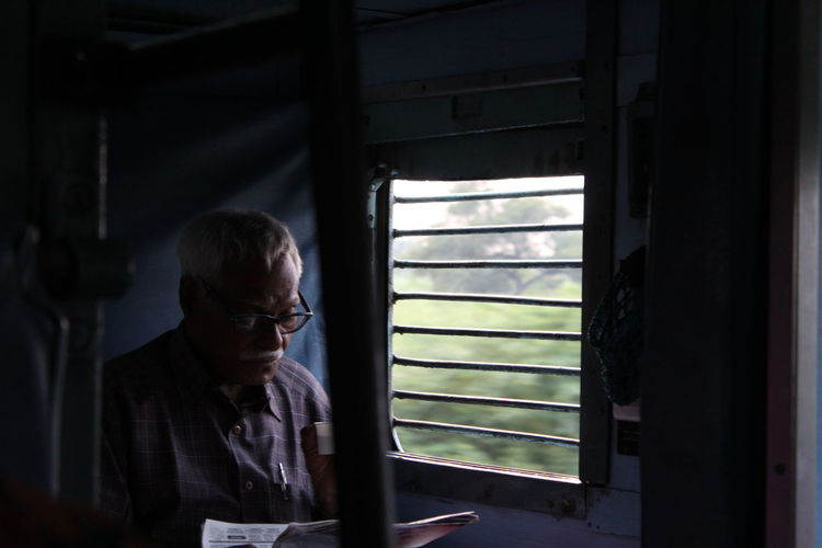 Senior man reading newspaper while traveling in train