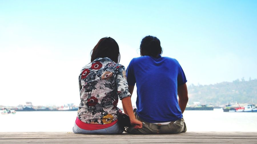 Rear View Of Couple Sitting On Jetty By River