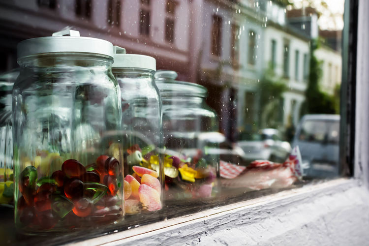 Close-Up Of Candies In Glass Jars Seen From Store Window