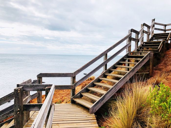 Staircase leading towards sea against sky