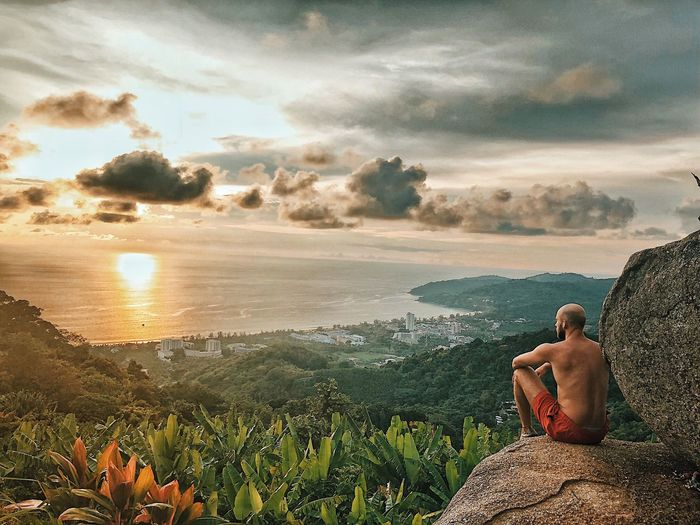 Shirtless man looking at sea while sitting on cliff against sky during sunset