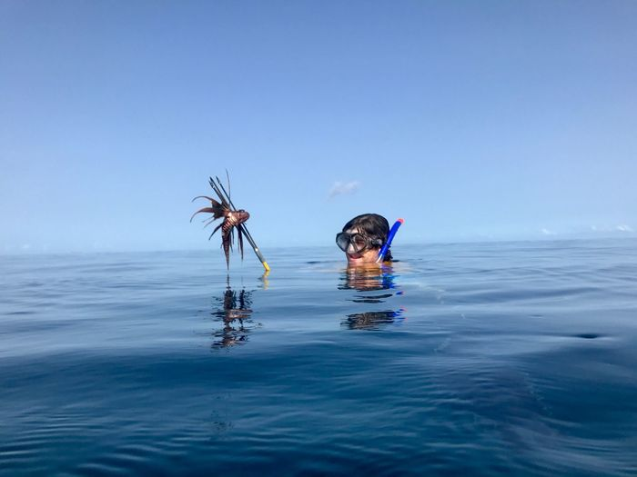 Man in sea against clear blue sky