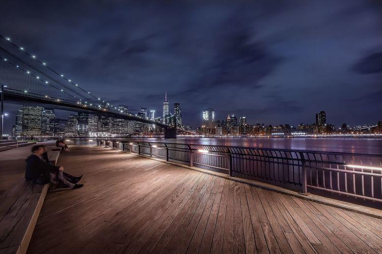 People sitting on pier against brooklyn bridge at night