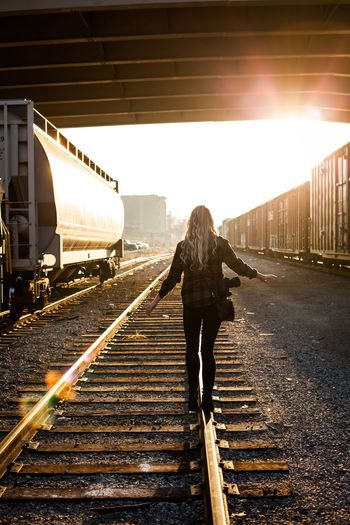 Rear View Of Woman Walking On Railroad Track On Sunny Day
